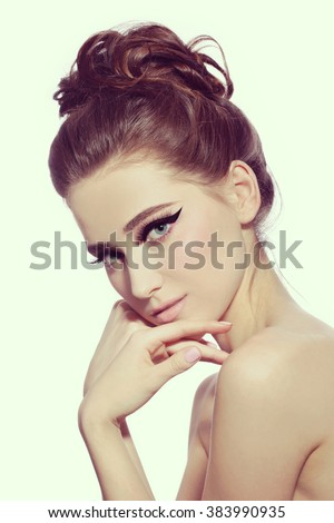 Vintage style portrait of young beautiful woman with fancy cat eye make-up and stylish hairdo  - stock photo