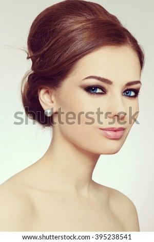 Vintage style portrait of young beautiful woman with stylish hair bun and smoky eyes - stock photo