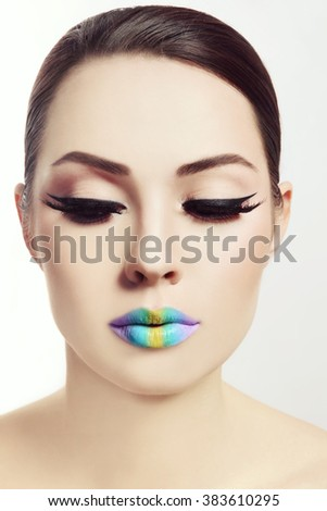 Vintage style portrait of young beautiful woman with winged eyes make-up and fancy rainbow ombre lips - stock photo
