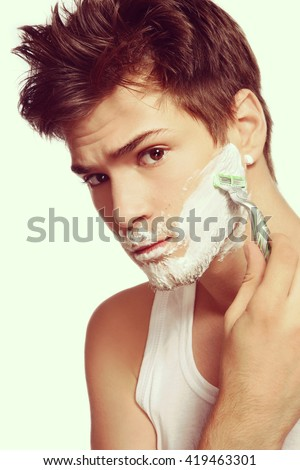 Vintage style portrait of young handsome sexy man shaving with razor
