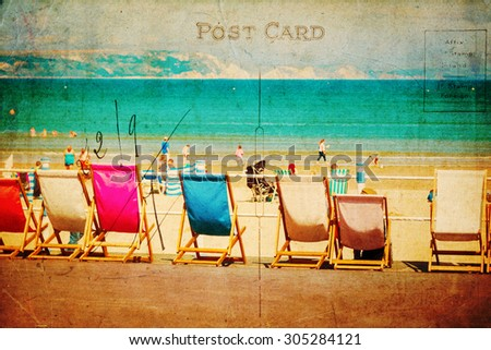 vintage style postcard with a row of deckchairs at a seaside promenade - stock photo