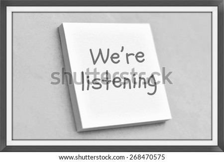 Vintage style text we're listening on the short note texture background - stock photo