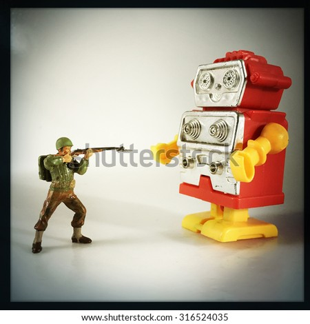 Vintage style Toy Soldier shooting at retro plastic robot - Instagram filtered  - stock photo
