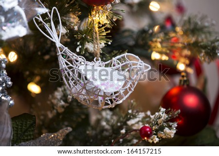 Vintage style wire bird ornament on Christmas tree - stock photo