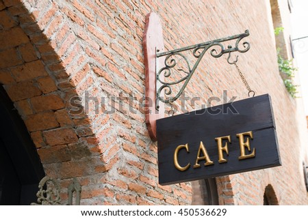 Vintage style wooden cafe sign on brick wall - stock photo
