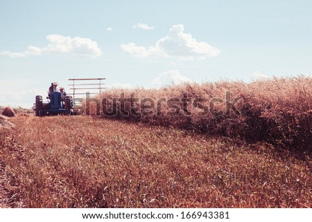vintage styled image of a tractor harvesting a crop - stock photo
