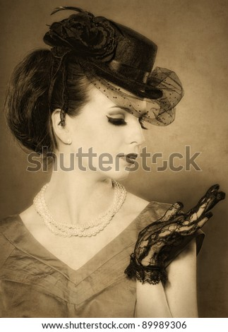 vintage styled portrait of a beautiful lady in hat with beads and lace gloves. - stock photo