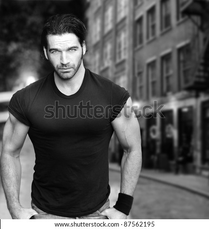 Vintage stylized black and white photo of young male model against city street - stock photo