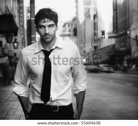 Vintage stylized black and white photo of young male model against city street (Photo has an intentional film grain) - stock photo