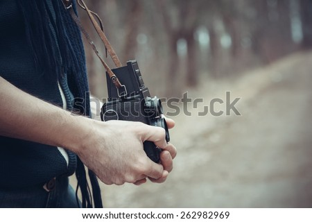Vintage stylized photo of hands of young man photographer with old camera.