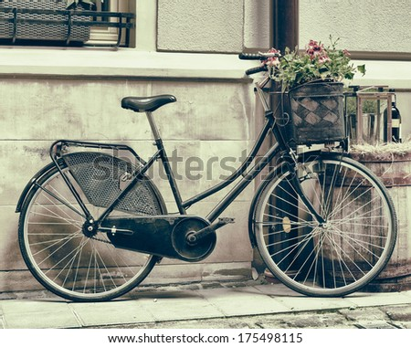 Vintage stylized photo of Old bicycle carrying flowers as decoration - stock photo