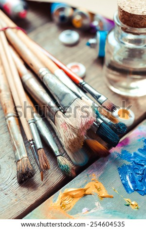 Vintage stylized photo of paintbrushes closeup, artist palette and multicolor paint tubes. - stock photo