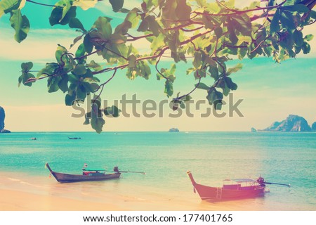 Vintage stylized photo of traditional longtail boats at Andaman sea, Thailand - stock photo