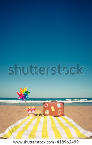 Vintage suitcase and beach items against blue sea and sky background. Summer vacation concept - stock photo