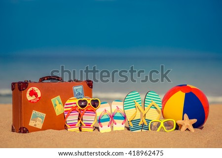 Vintage suitcase and flip-flops on sandy beach against blue sea and sky background. Summer vacation concept - stock photo