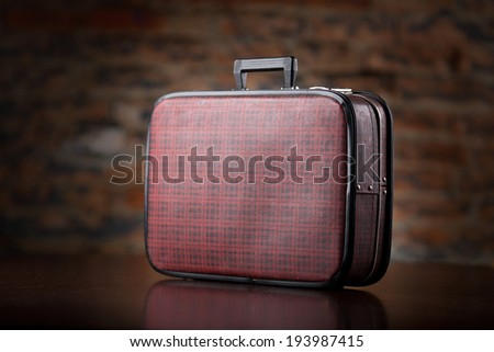 Vintage suitcase on wooden table - stock photo