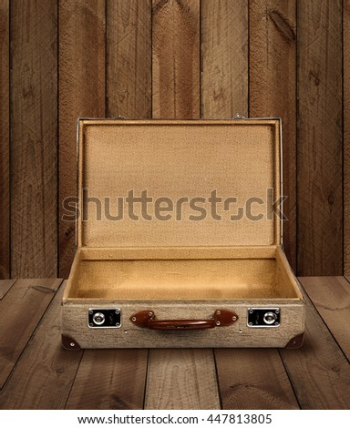 Vintage suitcase opened on rough wooden plank background - stock photo