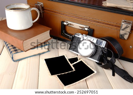 Vintage suitcase with books and camera on wooden background - stock photo