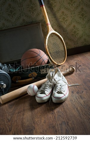 Vintage suitcase with sports equipment on wooden floor with canvas shoes on foreground. - stock photo