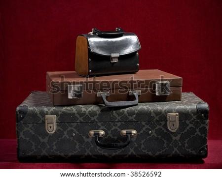 Vintage suitcases on red velvet - stock photo