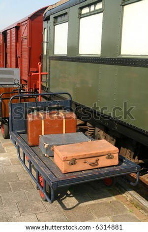 Vintage suitcases on trolley at the train-station with old traincars in the background
