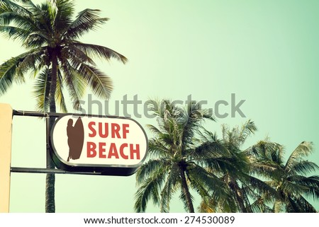 Vintage surf beach signage and coconut palm tree on tropical beach blue sky with sunlight of morning in summer,  instagram filter  - stock photo