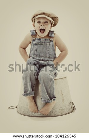 vintage surprise:  joyful little boy in overalls - stock photo