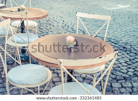 Vintage table and chairs in street cafe terrace in Alacati, Turkey. Toned - stock photo