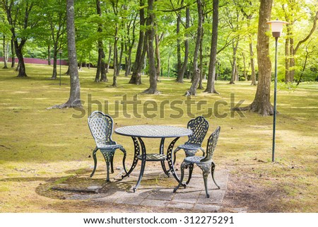 Vintage table and chairs set in a garden. peaceful relaxing serene tranquil setting - stock photo
