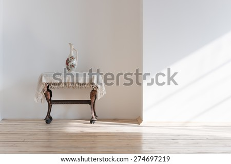 Vintage table and vase in sunlight - stock photo