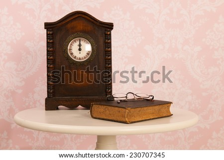 Vintage table in interior with old wall paper and clock - stock photo