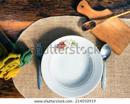 Vintage table setting with rustic dishes and cutlery on the old wooden background - stock photo