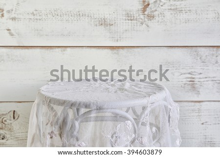 vintage table with lace table cloth. product display. selective focus
