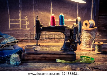 Vintage tailor workshop with sewing machine, cloth and scissors - stock photo