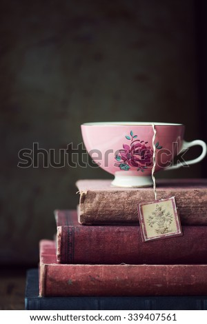 Vintage teacup on stack of old books - stock photo