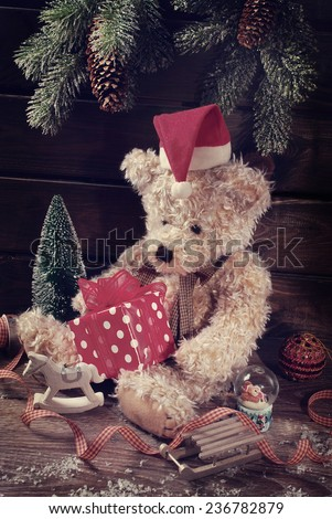vintage teddy bear in santa hat holding christmas gift box and sitting on wooden background  - stock photo