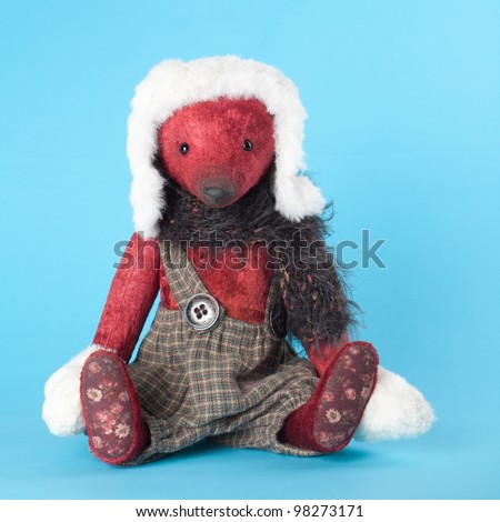 Vintage teddy bear with fur hat and mittens on blue background. Suitable for greeting cards. - stock photo
