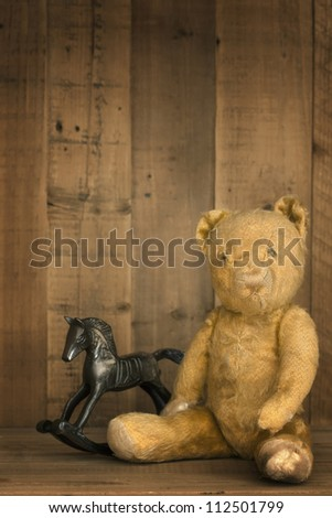 Vintage teddy bear with rocking horse, on wooden shelf. - stock photo
