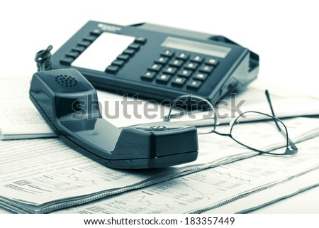 Vintage telephone handset on table with newspaper - stock photo