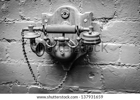 Vintage Telephone in Black and White mounted on an old wall - stock photo
