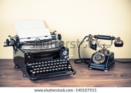 Vintage telephone, old typewriter on table - stock photo