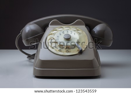 Vintage telephone on a white surface and dark background - stock photo