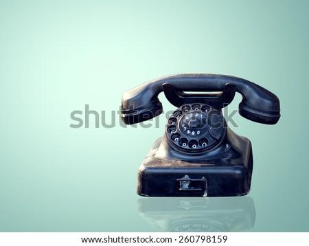 Vintage telephone on blue wallpaper  - stock photo