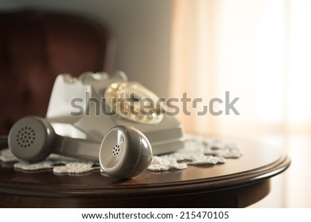 Vintage telephone on doily and round wooden table with handset on hold. - stock photo