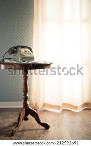 Vintage telephone on doily and wooden table in the living room next to a window. - stock photo