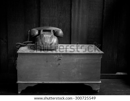 Vintage telephone on old table black and white still life photo. - stock photo