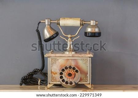 Vintage telephone on old table sepia photo. - stock photo