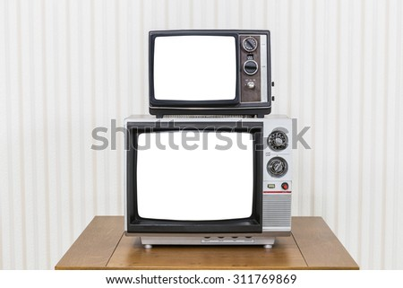 Vintage television stack on old wood table with cut out screens - stock photo