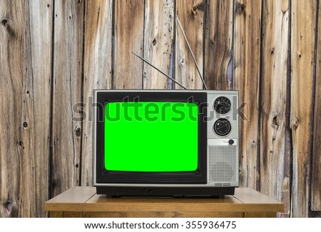 Vintage television with rustic wood wall and chroma key green screen.