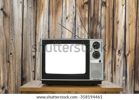 Vintage television with rustic wood wall and cut out screen.   - stock photo